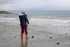 With great power comes great responsibility... (A No NY Mouse) Tags: boy boots spiderman hoodie beach sea sky cloud blue grey criccieth wales stones shore sand waves