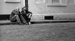 In the Gutter (Just Ard) Tags: street uk england people urban bw white man black men cup monochrome hat photography prime mono nikon bath sitting candid streetphotography 85mm somerset sit gutter nikkor unposed cobbles seated kerb primelens d7000 justard