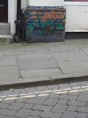 Camo column (Nekoglyph) Tags: street blue urban brown white black green shop peeling paint pavement yorkshire bricks richmond camouflage layers colourful cobbles doubleyellowlines