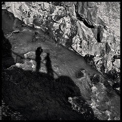 Photographers (Mika Latokartano) Tags: blackandwhite bw silhouette shadows river stream rockface