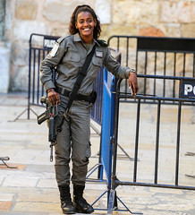 I think this is how Israel wants to think of itself: Armed but smiling on its borders. (ybiberman) Tags: israel jerusalem alquds christianquarter churchoftheholysepulchre girl soldier borderpolice armed m16 gun smiling barriers candid streetphotography cellphone smartphone adolescent