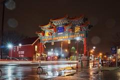 Spring showers at the Gate (beyondhue) Tags: rain weather somerset street long exposure chinatown gate gateway beyondhue night dark wet light lamp ottawa ontario canada art chinese entrance
