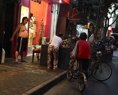 Twilight Street Shot Shanghai China Asia (eriagn) Tags: people man woman red hot dusk street backstreet cooking pavement candid lowlight bicycles warm floralprint twilight documentary streetshot night evening canon eos dailylife shanghai city china asia urban travel ngairehart ngairelawson eriagn photography outdoor landscape 上海市 buildings social town global colourful emotions feelings flickrsbest overtheexcellence streetlife blue everydaylife