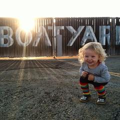 Boatyard girl. (eviloars) Tags: smile bar docks square restaurant rainbow toddler ramp san francisco leg curls squareformat blonde grin warmers dogpatch squatting sfist iphoneography instagramapp