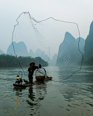 The Cormorant Fishermen of Guilin (Guangxi, China 2016) (Alex Stoen) Tags: action alexstoenphotography asia balance boat canoneos1dx china cormorant ef1635mmf28liiusm fisherman fishing fishingnet geotagged guilin mountains net netthrow river tradition travel vacation yangshuo iconic
