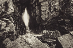 "B&W fine art - bright spring sunshine through the keyhole over milky water into the cliff cave, Collieston, Aberdeenshire, Scotland (grumpybaldprof) Tags: bw ""blackwhite"" monochrome sigma 1020 1020mm f456 ""sigma1020mmf456dchsm"" canon canon7d aberdeenshire scotland gordon nearaberdeen collieston ""seacaves"" cliffs rocks sea waves ""northsea"" smugglers smuggling spirits ""longexposure"" ""neutraldensity"" 400nd sky clouds granite colliestonspeldings ""sundriedfish"" coves ""lightattheendofthetunnel"" tunnel glare detail texture grey moody mood ""springsea"" foam movement seascape marine seaside seashore fineart flare contrast"