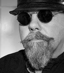 Hipster pose. (CWhatPhotos) Tags: hipster cwhatphotos face beard olympus four thirds camera photographs photograph pics pictures pic picture image images foto fotos photography artistic that have which contain me self selfie portrait jumper bush bushy full hairy chin goatee sepia black white mono mugshot man male leather pork pie hat head wear pointy round shades sunglasses sun glasses hipsterman pose smoothy smooth