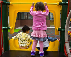 Playground Promotions 11 (ArdieBeaPhotography) Tags: infant preschool toddler child kids girl boy pink red green climb slide swing throw ball playground plastic jackets tights skirt jumper top reach squat play together