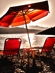 A Beach in Greece (jezselten) Tags: red sun sunlight holiday reflection beach water umbrella walking table happy europe chairs stones relaxing hills greece