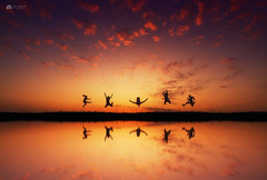 Jump... (Kerriemeister) Tags: composite composition dreamlike fantasy imagination colourful sunrise reflection reflections water sky cloud clouds people silhouette silhouettes fun photoshop photomanipulation digital art create coast holidays bank creative